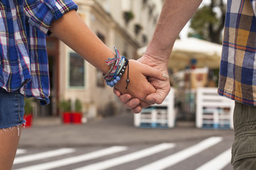 Close-up of the holding hands of a young couple.