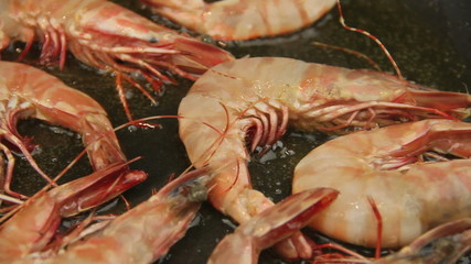 Whole shrimps being fried in a fry pan with hot oil.