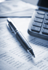Calculator, pen and money on financial statement