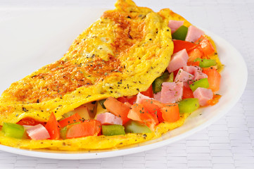 Delicious omelet with tomato, pepper, ham, basil