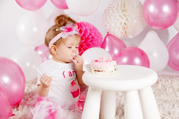 Baby eating the birthday cake with fingers
