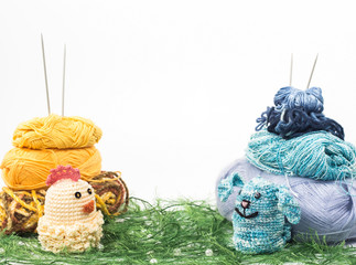 Knitted toys on background skeins