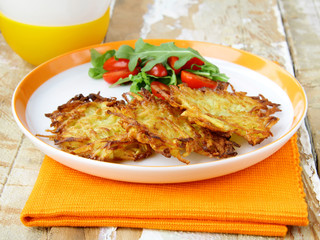 potato pancakes served with salad and sour cream