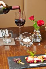Bedienung gießt Glas Rotwein ein
