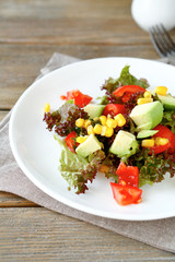 Summer salad with avocado, tomatoes and corn on a white plate