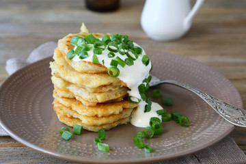 Potato pancakes with sour cream and green onions