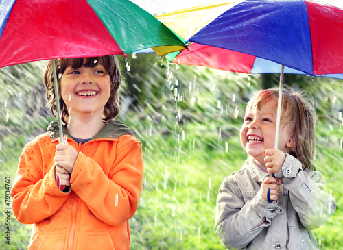 two happy brother with umbrella outdoors - 79134760