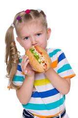 Little girl eats hot dog
