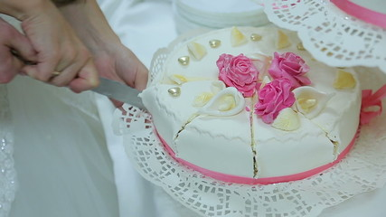The bride and groom cut the cake together holding a knife