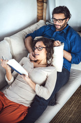 Young couple reading book on couch at home