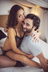 Young beautiful couple in sensual games in bed