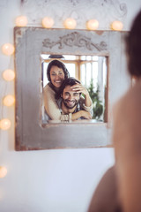 Young couple playing in front of a mirror