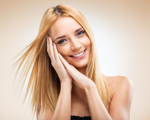 Beautiful blonde woman with hands in the face of