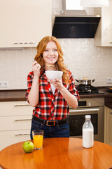 Young pretty smiling woman having a bowl of cereal with milk for