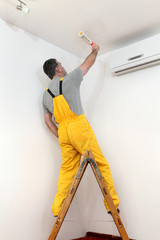 Worker painting ceiling from ladder with paintroller