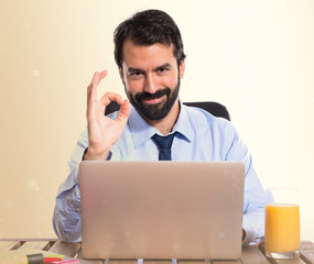 Businessman in his office making Ok sign