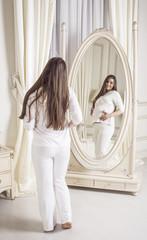 beautiful pregnant woman European standing, room