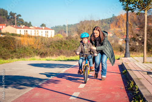 Mother teaching son to ride a bike in cycleway - 79143509