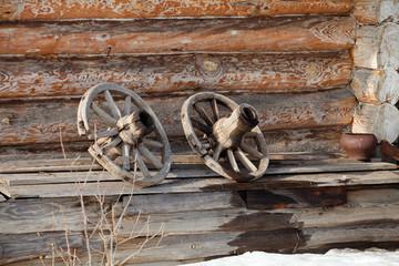 Деревянные колеса на фоне стены деревенского дома