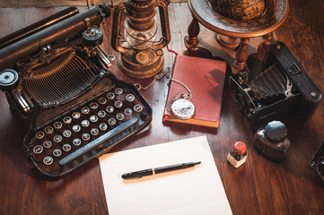 Vintage items, camera, pen, globe, clock, typewriter on the old