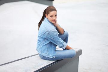 Schönes Mädchen sitzt auf Mauer