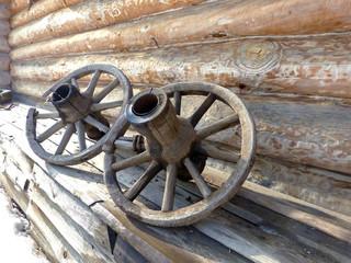 Старые деревянные колеса на фоне стены деревенского дома