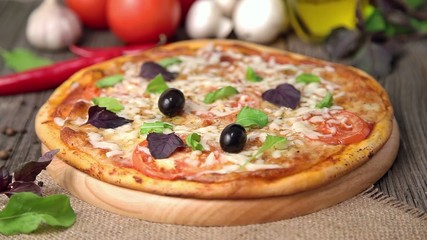 Unrecognizable woman is putting olives on pizza margherita