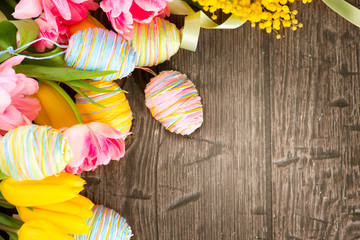 Easter background decorated with colourful eggs and tulips