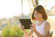 Happy woman using a tablet outdoors - 79146186