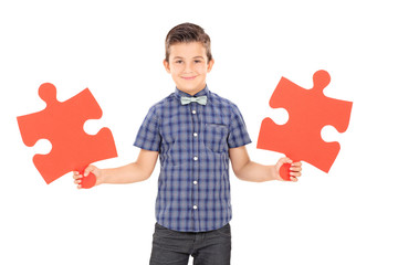 Kid holding two pieces of a puzzle