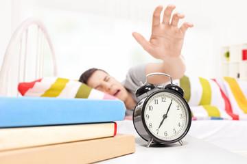Sleepy man reaching for the alarm clock