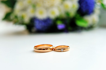 wedding rings with flowers on background