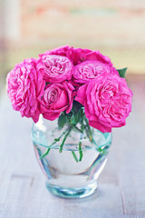 Beautiful fresh roses in a vase on a table.