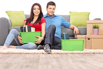Young couple sitting on the floor with moving boxes