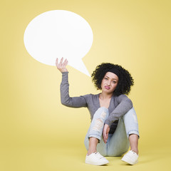Bugged girl holding a white speech balloon with copyspace.