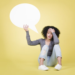 Desperate girl holding a blank white speech balloon.