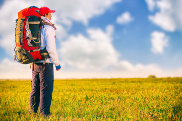 Hiker with backpack standing in the field