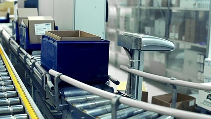 Cardboard boxes are weighed on a transporter of a packaging line