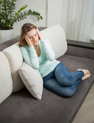 woman lying on sofa and suffering from headache