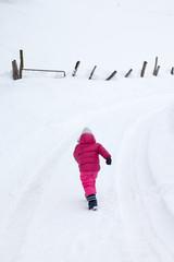 Bambina che corre sulla neve