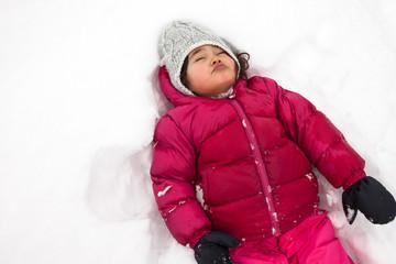 bambina sdraiata sulla neve