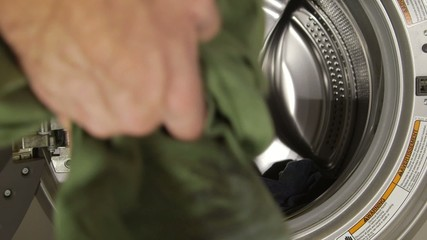 Man putting dirty clothes in washing machine - Lifestyle concept
