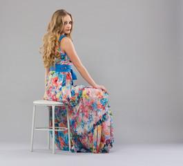 Beautiful young woman sitting in a trendy long dress