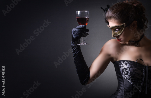 young woman in carnival mask and a glass of red wine. - 79158325