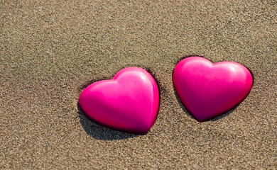 Two red hearts on the beach symbolizing love