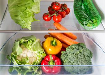 Geöffneter Kühlschrank gefüllt mit Obst und Gemüse