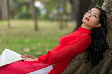Slender young Vietnamese woman relaxing in a park