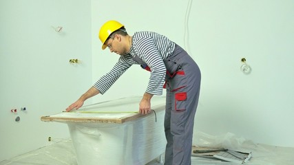 Workman measuring bathtub in new apartment interior