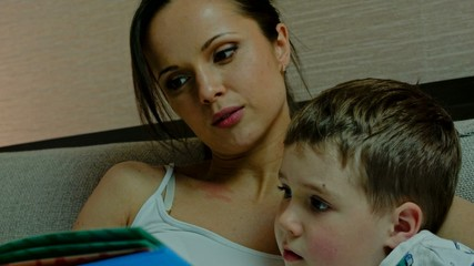 Young mother and her son reading book in a bed