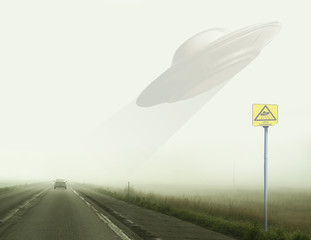 Rise of the UFO over the road during fog.